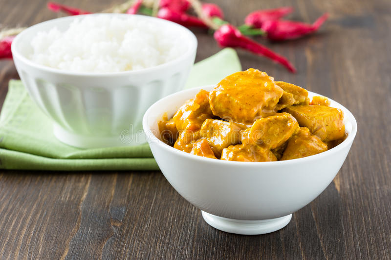 Chicken curry with rice. In white bowl on wooden table stock image