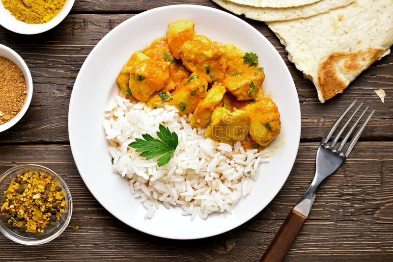 Chicken curry with rice, top view. Chicken curry with rice on wooden background. Top view, flat lay stock photo