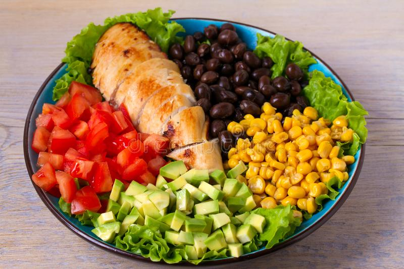 Chicken dish with nutritious selection of vegetables: avocado, beans, tomatoes and sweet corn. Chicken breast salad. stock photography