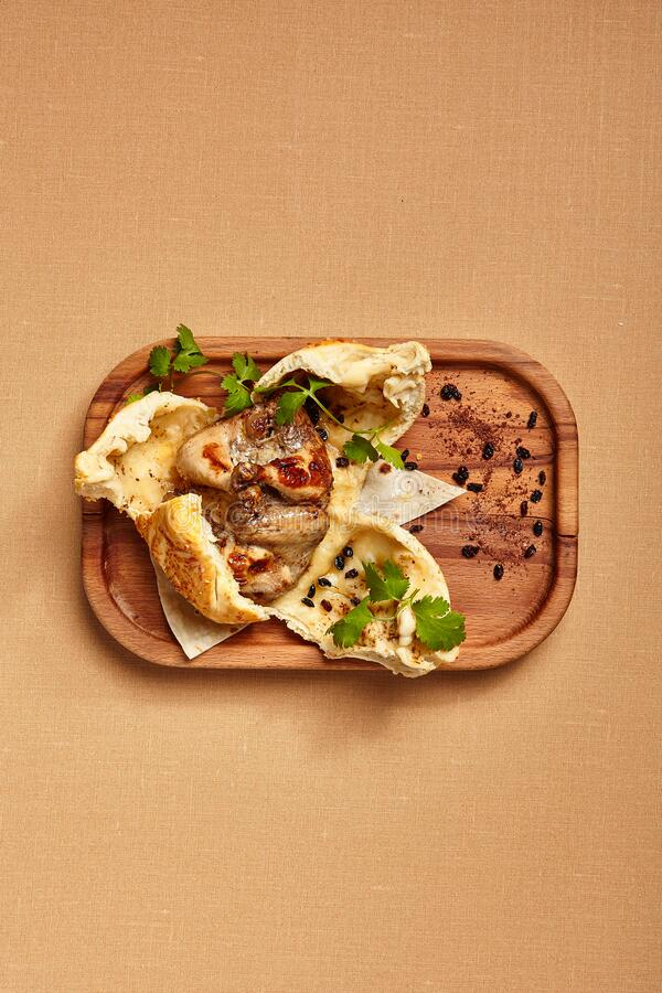 Chicken in dough served on wooden tray stock image