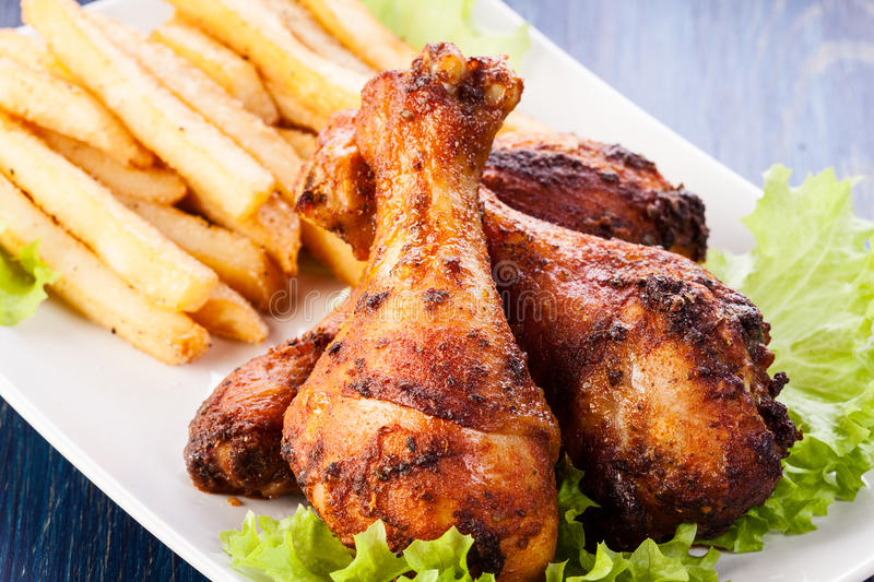 Chicken drumsticks with chips royalty free stock photos