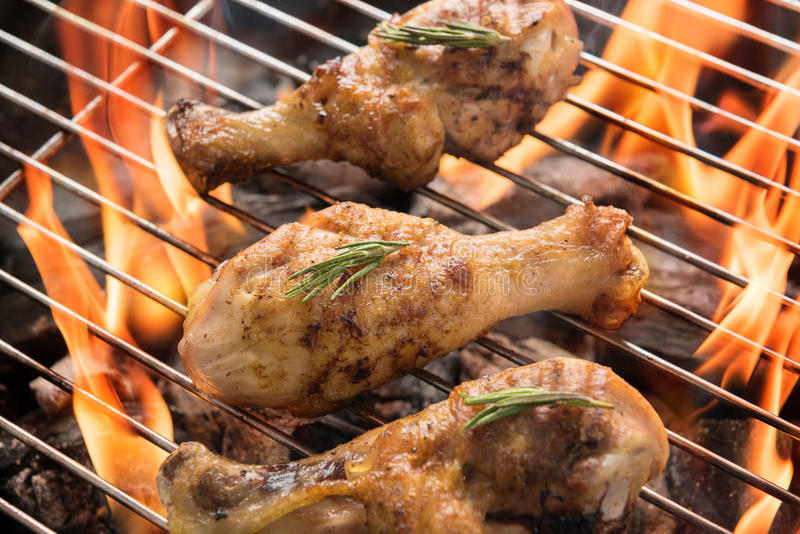 Chicken drumsticks grilling over flames on a barbecue.  royalty free stock photography