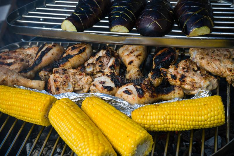 Chicken drumsticks with vegetables: sweet corn and aubergines on barbecue grill with fire stock photo