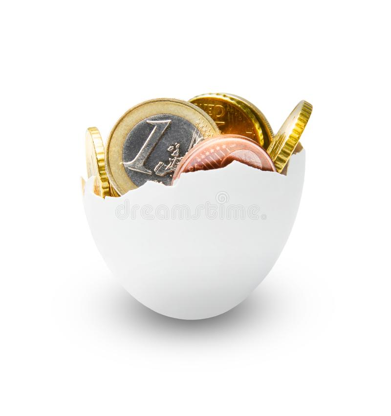 Chicken egg shell filled with euro coins. Symbol of finance, accumulation and wealth or something else. White background royalty free stock photography