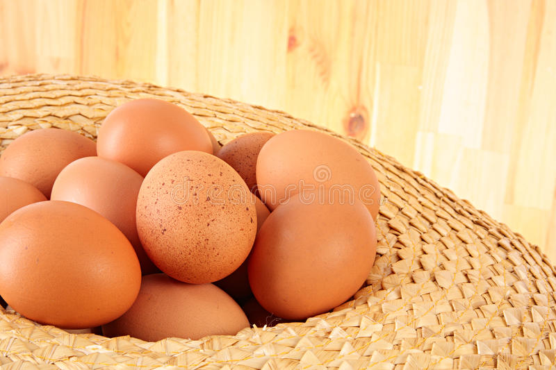 Chicken eggs. Strawy hat full of chicken eggs royalty free stock photography
