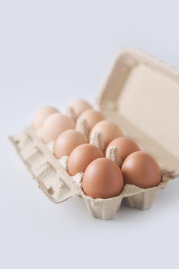Chicken eggs are arranged in a gradient color tone in eco carton on white background. Perspective view stock photo