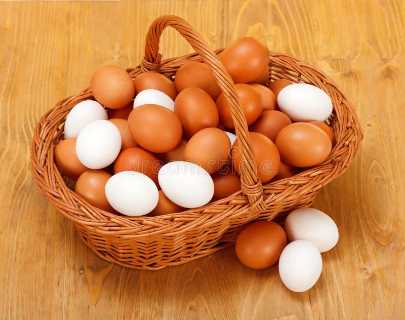 Chicken eggs in basket stock photos