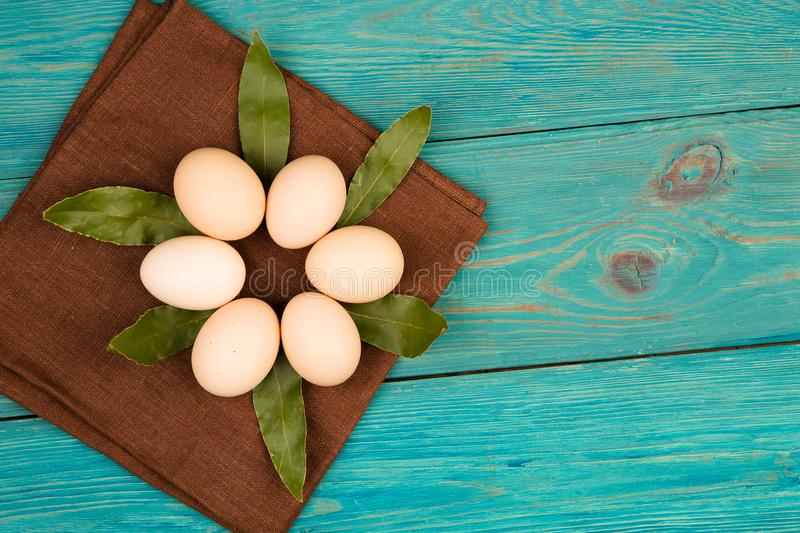 Chicken eggs, bay leaf and brown linen napkin on wooden table royalty free stock photography