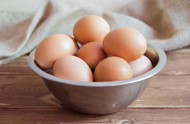 Chicken eggs in a metal bowl on a wooden table royalty free stock image