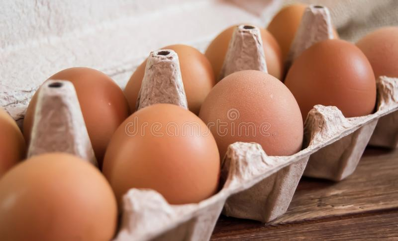 Chicken eggs in the package on wooden background stock images