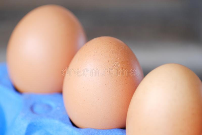 Chicken eggs in the purple package on the table royalty free stock photos