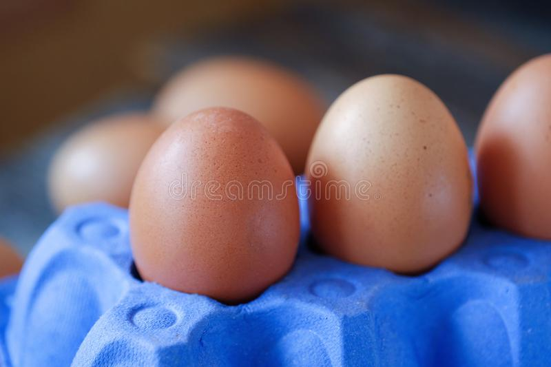 Chicken eggs in the purple package on the table royalty free stock photography
