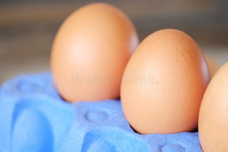 Chicken eggs in the purple package on the table stock image
