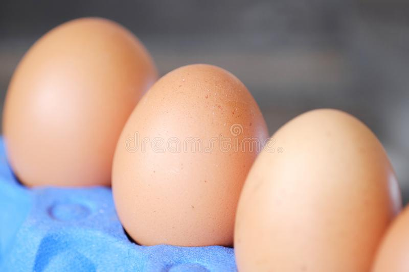 Chicken eggs in the purple package on the table royalty free stock image