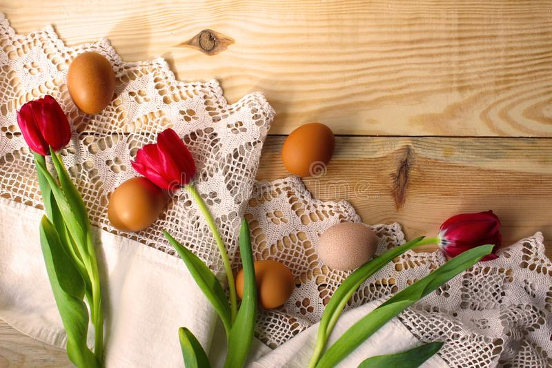 Chicken eggs, red tulips on a white crocheted tablecloth. Chicken eggs on a white crocheted tablecloth. red tulips. Rustic style. The concept of Easter, rustic royalty free stock photo