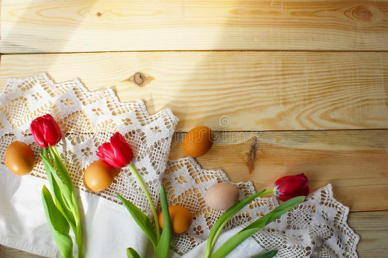 Chicken eggs, red tulips on a white crocheted tablecloth. Chicken eggs on a white crocheted tablecloth. red tulips. Rustic style. The concept of Easter, rustic stock photography