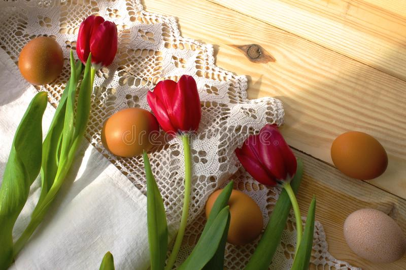 Chicken eggs, red tulips on a white crocheted tablecloth. Chicken eggs on a white crocheted tablecloth. red tulips. Rustic style. The concept of Easter, rustic royalty free stock images