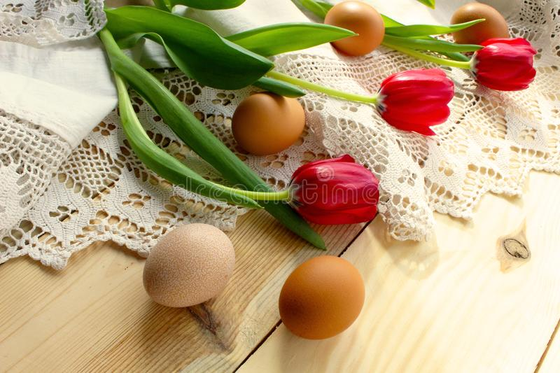Chicken eggs, red tulips on a white crocheted tablecloth. Chicken eggs on a white crocheted tablecloth. red tulips. Rustic style. The concept of Easter, rustic royalty free stock photos