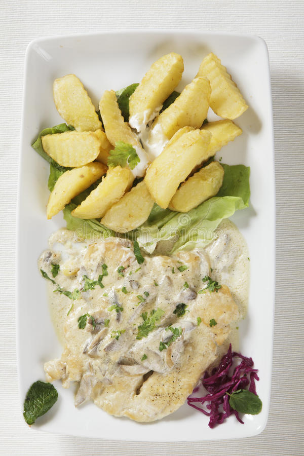Chicken escalope with white wine sauce and patatoes. Top view of a very delicious chicken meal escalope with white wine sauce and mushrooms and patatoes served stock photography