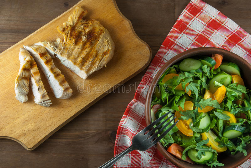 Chicken fillet, grilled, with a large portion of salad. With fresh vegetables and herbs on a wooden table with a red cloth into a cell. top view stock photography