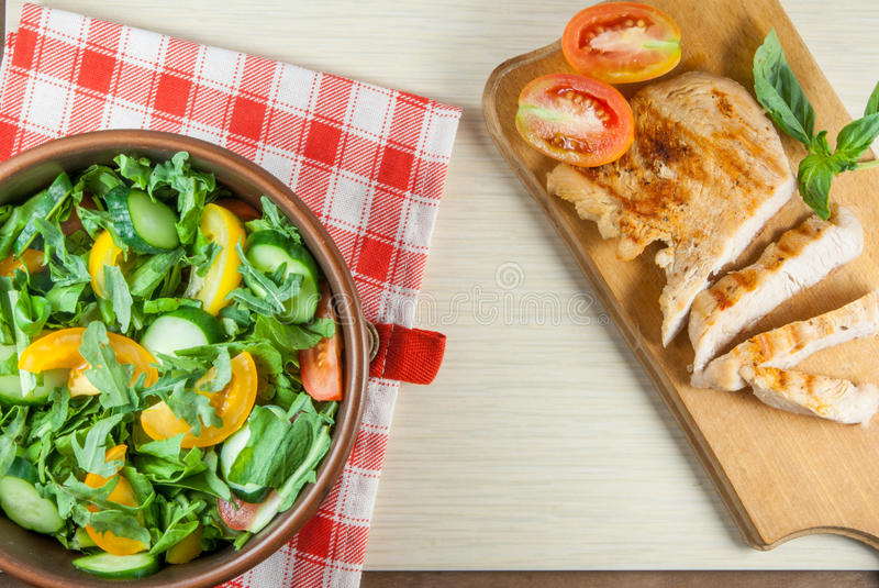 Chicken fillet, grilled, with a large portion of salad. With fresh vegetables and herbs on a wooden table with a red cloth into a cell. top view stock images