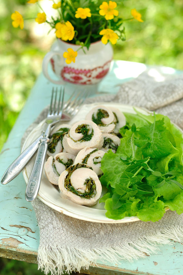 Chicken fillet rolls with fresh greens served with salad leaves, copy space for your text royalty free stock image