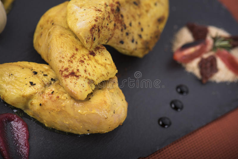 Chicken fillet served with pumkin puree and baked potatoes on a slate plate 12close up shot stock image