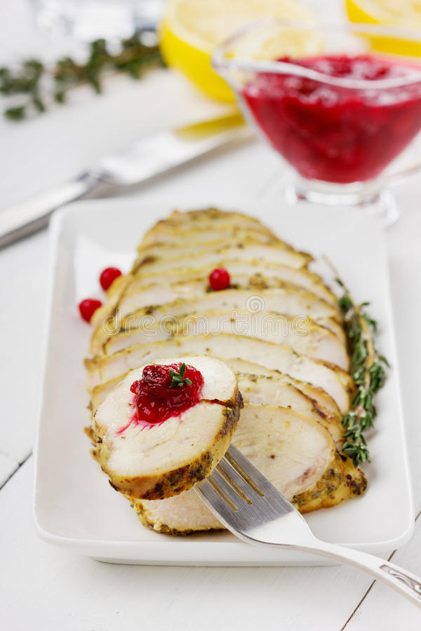 Chicken fillet slices with thyme and cranberry sauce with lemon stock images
