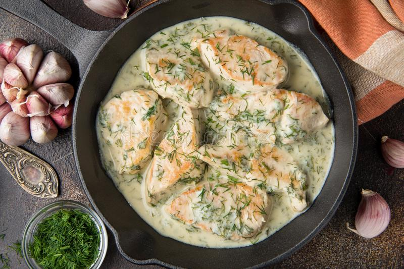 Chicken fillet or Turkey breast in creamy sauce with dill and garlic, in cast iron black pan on dark background. Delicious royalty free stock images