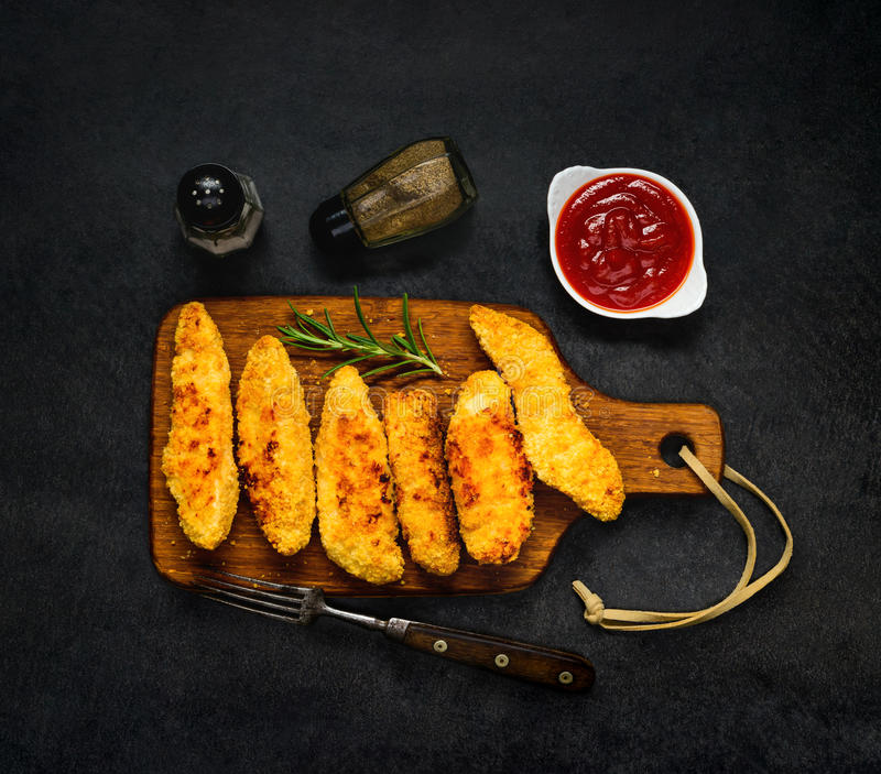 Chicken Fingers with Ketchup and Condiments. Dinner Table with Chicken Fingers, Ketchup and Condiments in Top View royalty free stock image