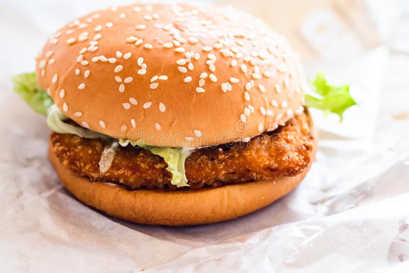 Chicken fried burger with fresh vegetable fast food on white paper background.  stock images