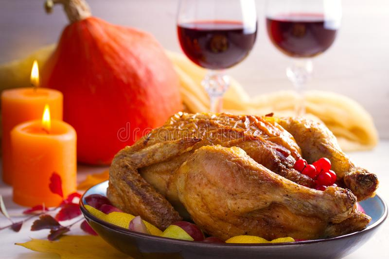 Chicken with fruits and berries on white table, decorated with autumn leaves, candles and pumpkin. Two glasses of red wine. Cozy atmosphere of autumn or royalty free stock images