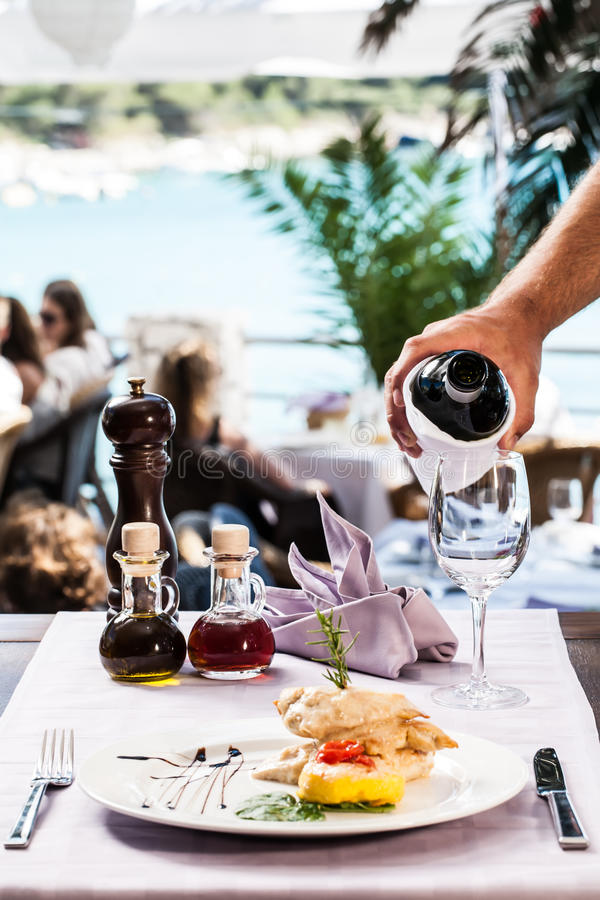 Chicken gourmet and white wine. Chicken fillet and potato fritter gourmet dish with a crisp glass of wine being poured by the waiter stock photo