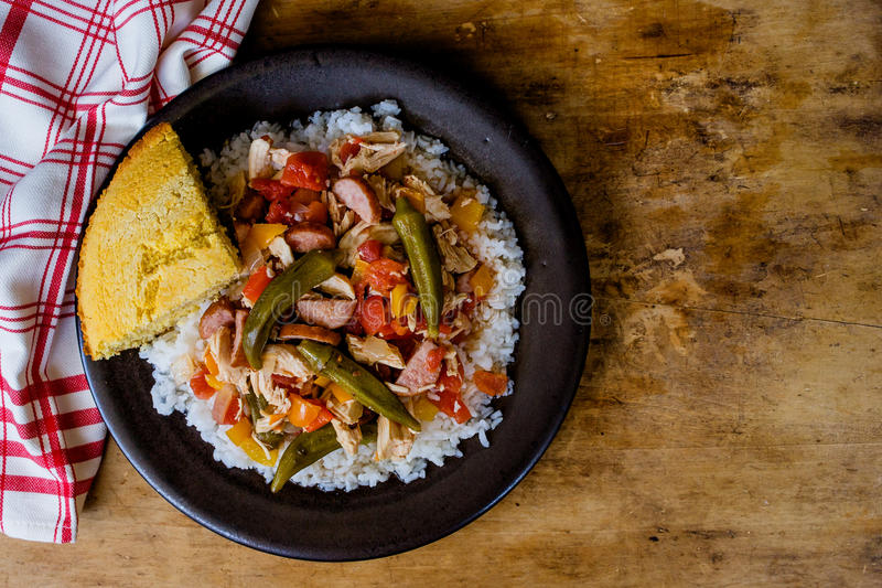 Chicken Gumbo With Cornbread. A big bowl of chicken gumbo with whole okra served over rice. Red and white napkin and a slice of cornbread royalty free stock photography