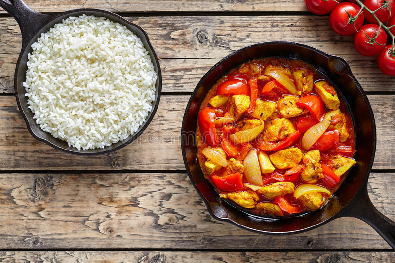 Chicken jalfrezi dietetic traditional Indian curry spicy fried meat with vegetables and basmati rice food. In cast iron pan on vintage table background stock photography