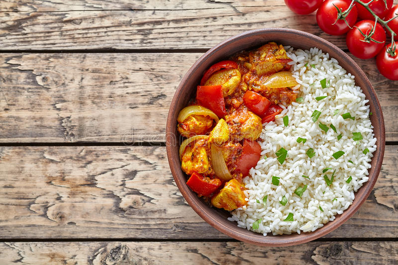 Chicken jalfrezi traditional Indian spicy curry chilli meat with basmati rice and vegetables. Healthy dietetic asian food in clay dish on vintage table stock photography