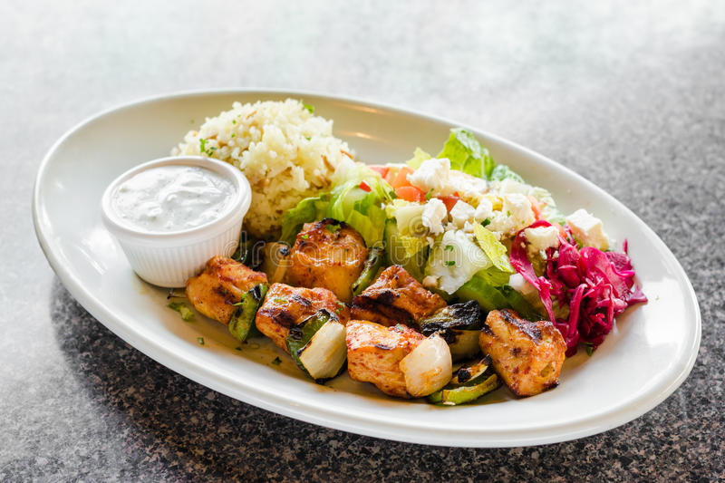 Chicken Kebab Plate. With Greek Salad with tomatoes, olives, lettuce, goat cheese, red cabbage, cucumbers, salad dressing and ranch on a white plate on a black royalty free stock images