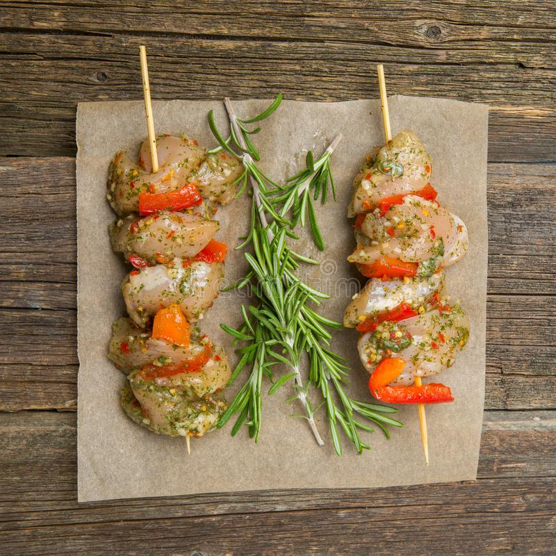 Making kebabs from chicken - raw meat on skewers royalty free stock images