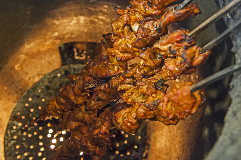 Chicken kebabs cooking in a tandoori oven royalty free stock photography