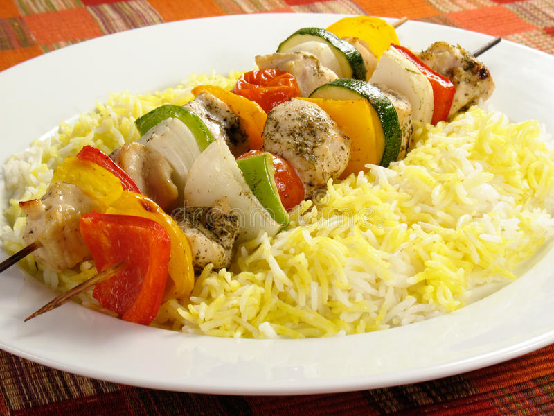 Chicken Kebabs and Rice. Seasoned chicken kebabs with bell peppers, onions, zucchini, and cherry tomatoes. Accompanied by a bed of saffron flavored basmati rice royalty free stock images