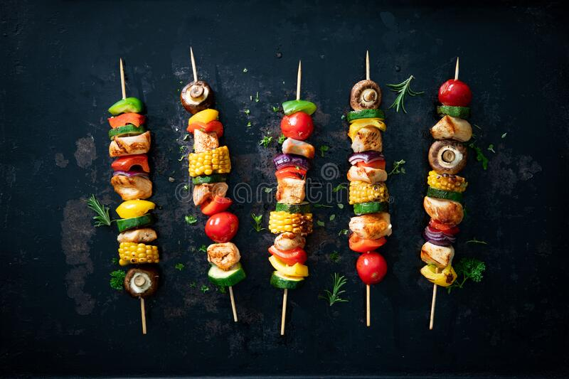 Chicken kebabs on skewers with mushrooms and vegetables royalty free stock photography