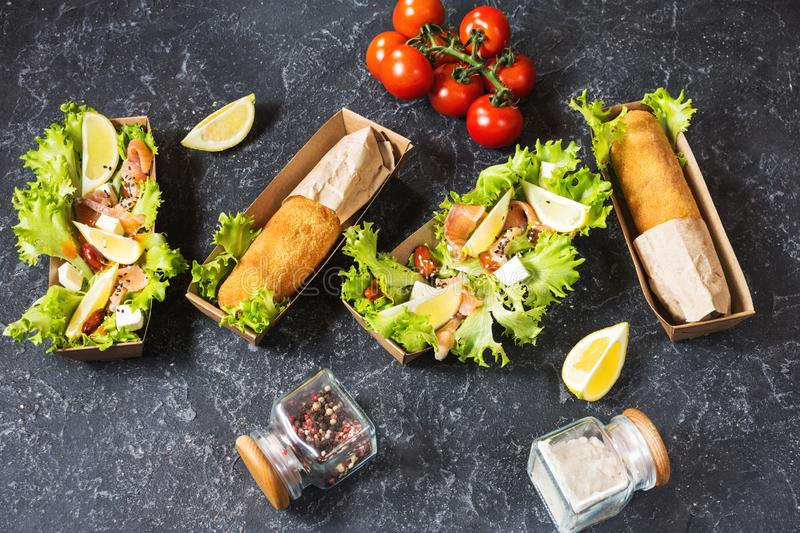 Chicken Kiev cutlets and Salad with smoked salmon in takeaway Box. royalty free stock photo