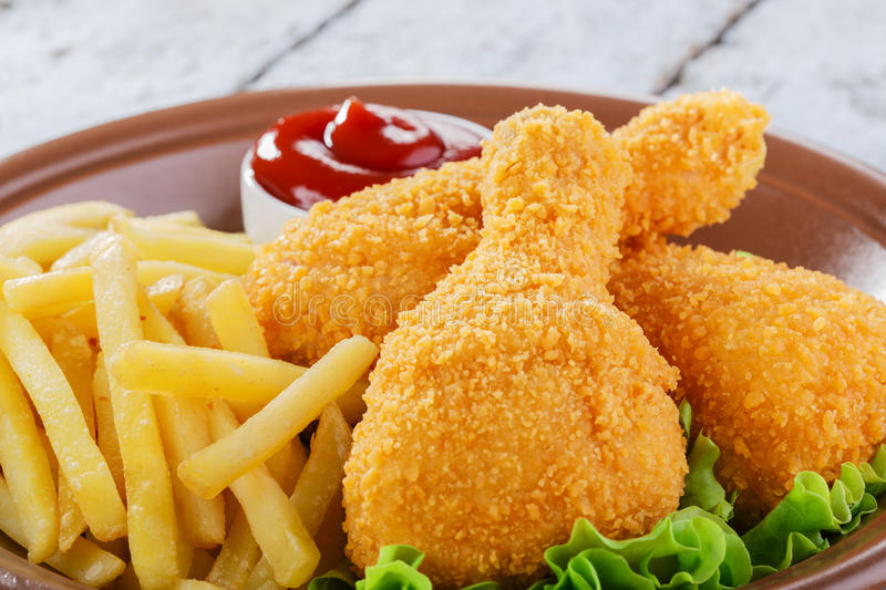 Chicken leg breaded. And fried potatoes stock images