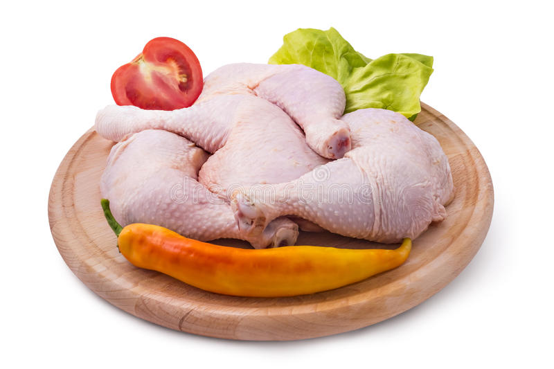 Chicken leg quarters. Fresh raw chicken legs arrangement on kitchen cutting board with lettuce, tomato and pepper royalty free stock photography
