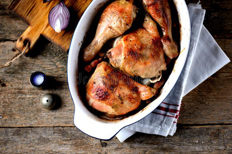 Chicken legs baked with fresh rosemary and pepper on an old wooden background. Rustic style. stock images