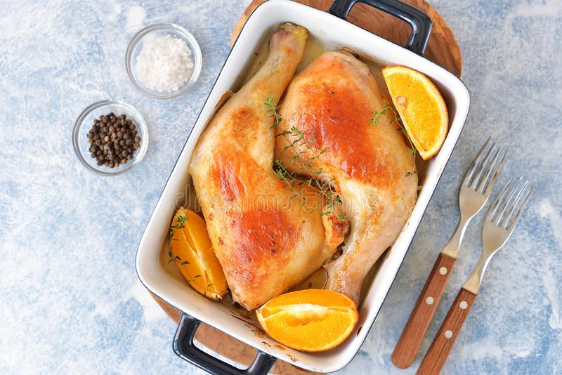Chicken legs baked with orange slice and rosemary. Top view. royalty free stock photos