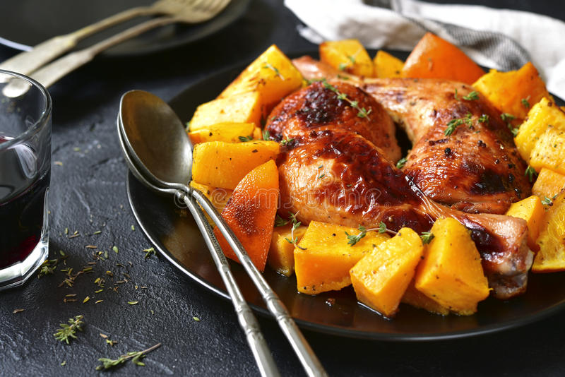 Chicken legs baked with pumpkin and orange. stock image