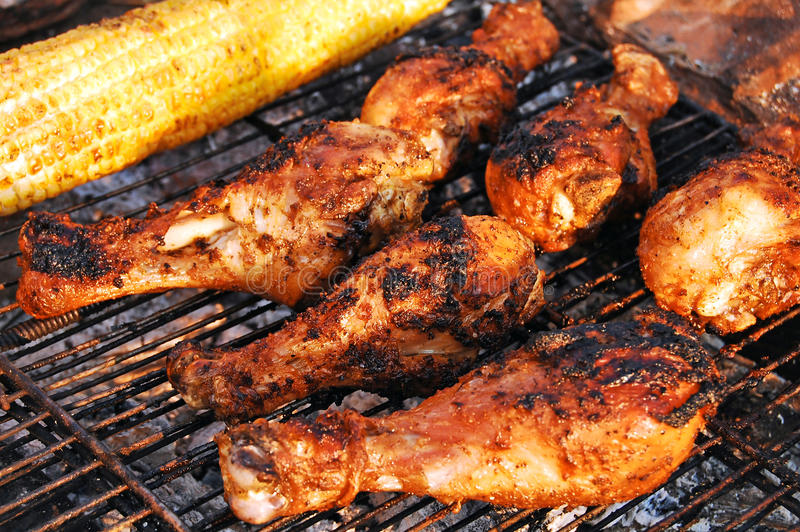 Chicken legs and corn on grill
