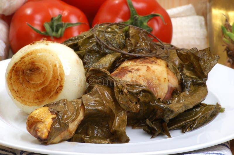 Chicken legs grilled in wine leaves. Chicken legs grilled in organic wine leaves royalty free stock photos