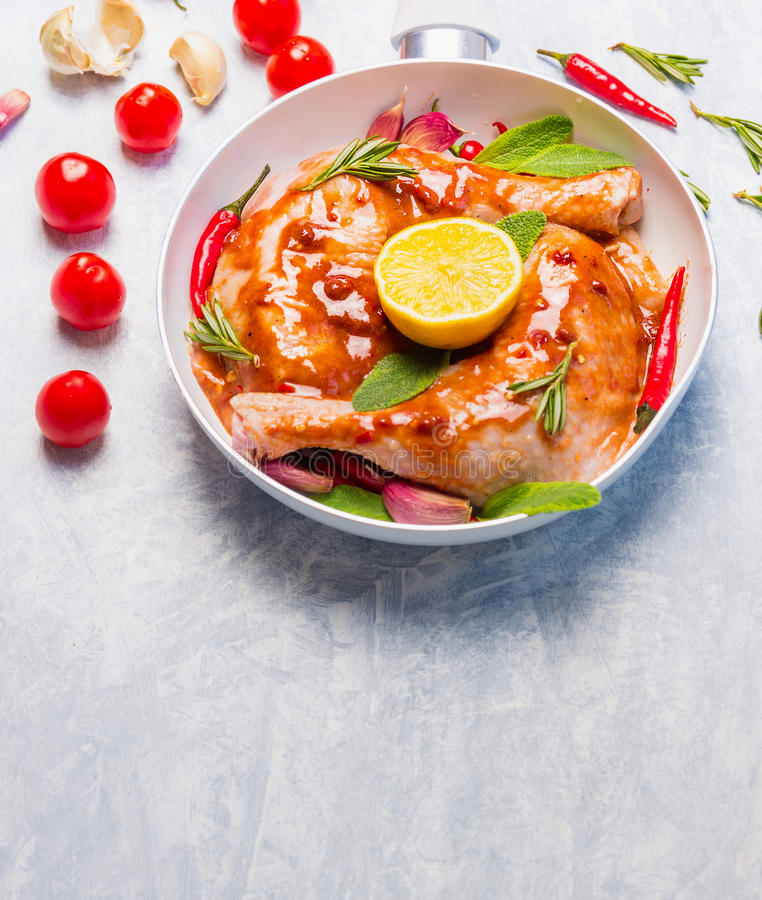 Chicken legs with hot red spicy marinade, lemoon and sage in white frying pan. Place for text stock photo